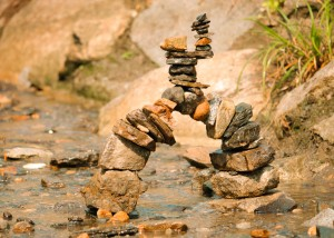 Zen tower bridge of different coloured stones in a shallow stream